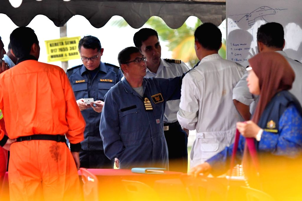MUAR(MALAYSIA), March 22, 2018 Rescuers discuss the rescuing of the missing crew members of a capsized sand dredger, in Parit Jawa in southern Malaysian state of Johor, on March 22, 2018. ...