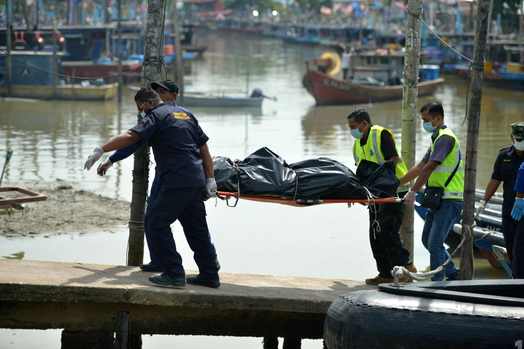 MUAR(MALAYSIA), March 24, 2018 Rescuers transfer a body found inside the capsized dredger in Muar in southern Malaysian state of Johor, on March 24, 2018. Rescuers searching for the ...