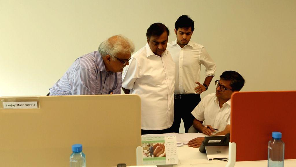 "Mukesh Ambani, standing centre, with son Akash Ambani, at his left, confidant Manoj Modi, seated, and human resource head Sanjay Jog, at the Reliance Jio open office on the 7th floor of ""TC22"" ... - Akash Ambani and Manoj Modi"