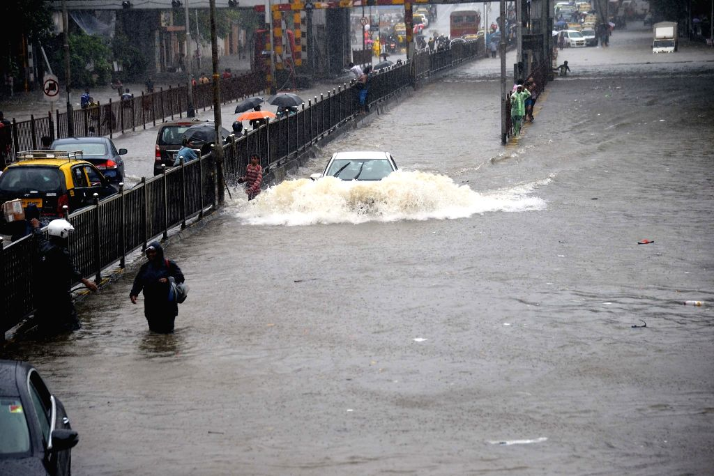 Mumbai: A car wades through the inundated King's Circle during rains in Mumbai, on July 1, 2019. (Photo: IANS)