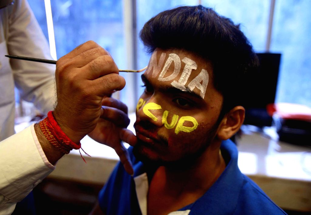 A cricket fan gets his face painted ahead of ICC World Cup 2015 in Mumbai, on Feb 11, 2015.