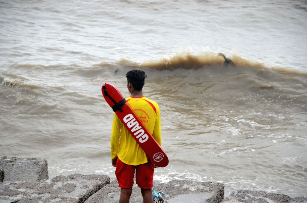 Mumbai: A life guard on duty at a sea beach in Mumbai on June 13, 2019. Life guards on beaches across the city have been asked to ensure that nobody ventures into the sea, in the wake of Cyclone Vayu. (Photo: IANS)