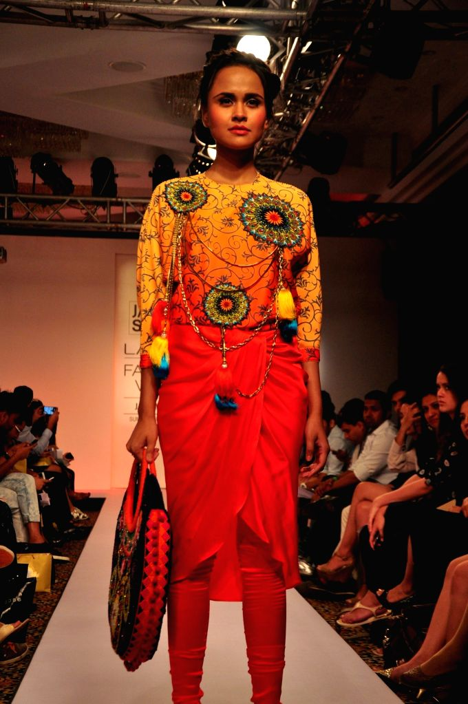 A model walks the ramp displaying an outfit by designer Neha Agarwal at the Lakme Fashion Week Summer Resort 2015 in Mumbai, on March 21, 2015
