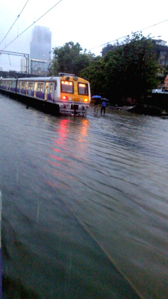 A trian runs on a submerged track as heavy rain hit train services in Mumbai on June 19, 2015.