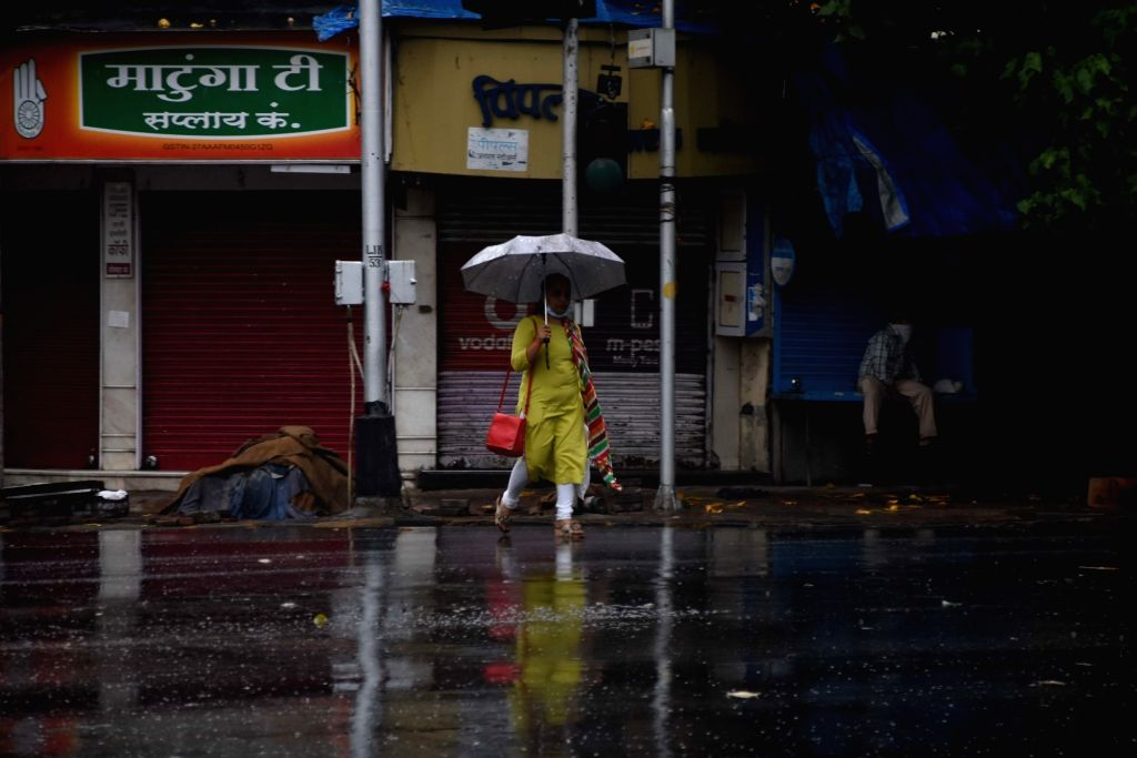 Mumbai: A woman sheilds herself using an umbrella during rains in Mumbai on June 1, 2020. (Photo: IANS)