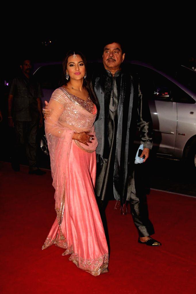 Actor Shatrugan Sinha along with his daughter Sonakshi Sinha during his son Kush wedding reception in Mumbai, on Jan. 19, 2015. - Shatrugan Sinha and Sonakshi Sinha