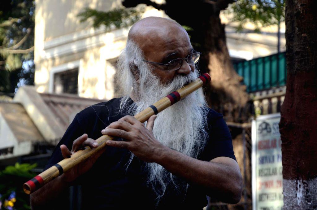 Architect Suhas Joshi plays flute at Shivaji Park in Mumbai, on Feb 7, 2015.