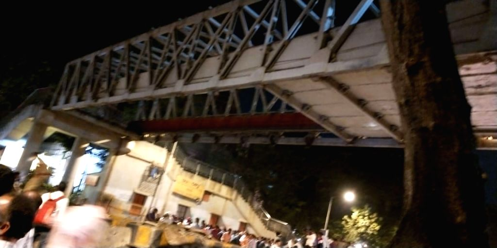 Mumbai: At least two commuters were injured when a portion of a pedestrian bridge crashed near the Chhatrapati Shivaji Terminus in Mumbai on March 14, 2019. (Photo: IANS)