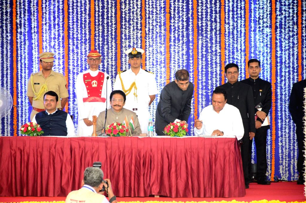 Mumbai: BJP Mumbai President Ashish Shelar in the presence of Maharashtra Governor CH Vidyasagar Rao and Chief Minister Devendra Fadnavis, signs after taking oath as a Cabinet Minister during a swearing-in ceremony, in Mumbai, on June 16, 2019. (Phot - Devendra Fadnavis and Vidyasagar Rao