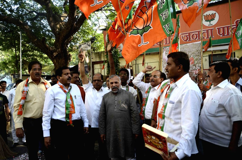 BJP workers celebrate party's performance in Jharkhand and Jammu and Kashmir Assembly polls at party head quarter in Mumbai on Dec 23, 2014.