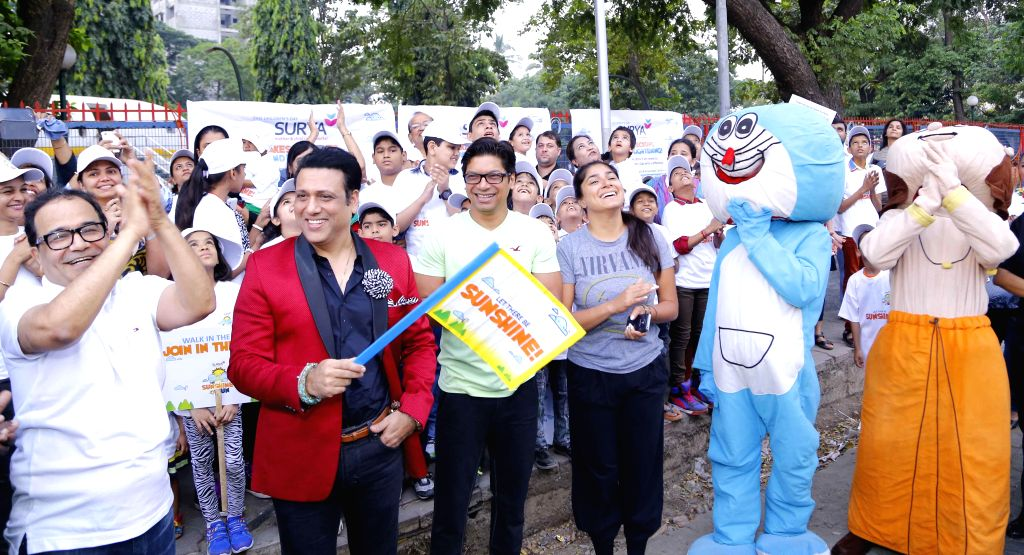 Dr. Bhupendra Avasthi, actor Govinda and singer Shaan with wife Radhika during the walkathon organized by Surya Sunshine Child Care Hospital on the occasion of Children's Day in Mumbai, on ...