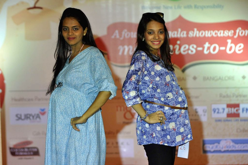 Expecting mothers walk the ramp during a expecting mothers fashion show organised by Cordlife in Mumbai on March 15, 2015.
