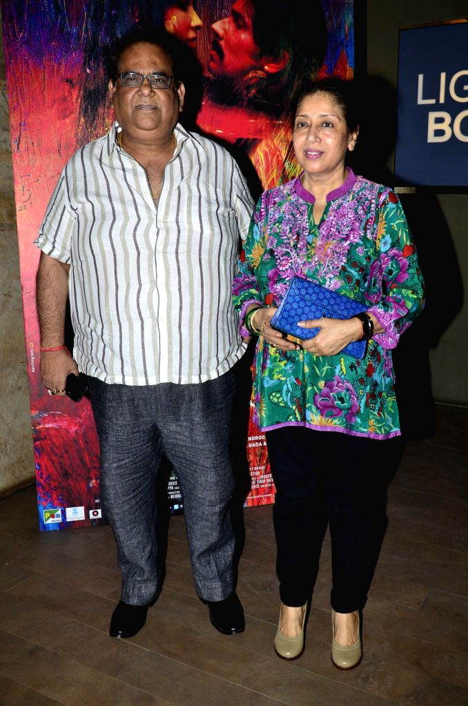 Filmmaker Satish Kaushik with his wife during the screening of film Rang Rasiya, in Mumbai, on Nov. 4, 2014. - Satish Kaushik