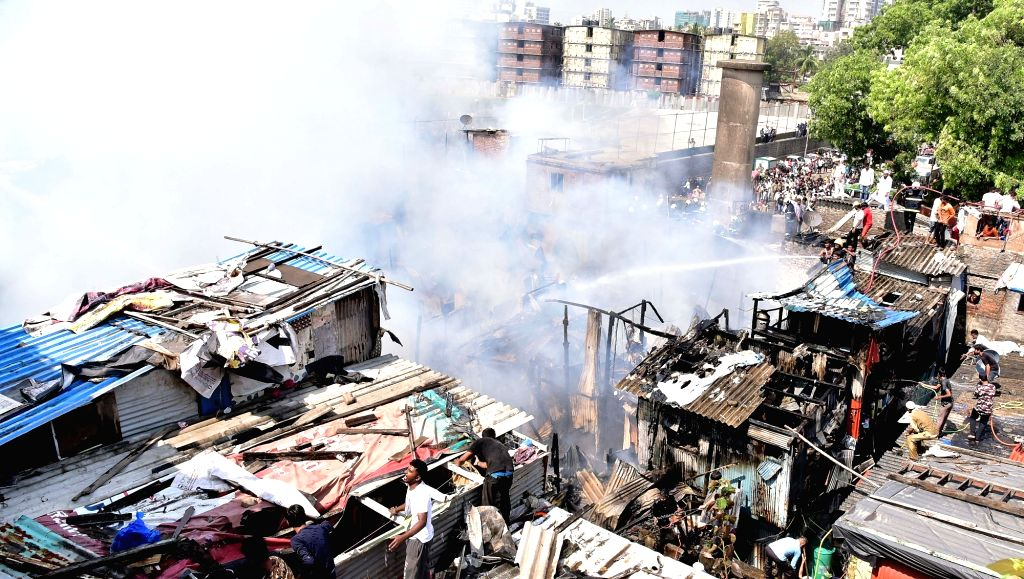 : Mumbai: Fire fighting operations underway at a slum where fire broke out in Bandra, Mumbai on Oct 30, 2018. Fire broke out around 12 noon in Bandra west's Nargis Dutt slum followed by over ...