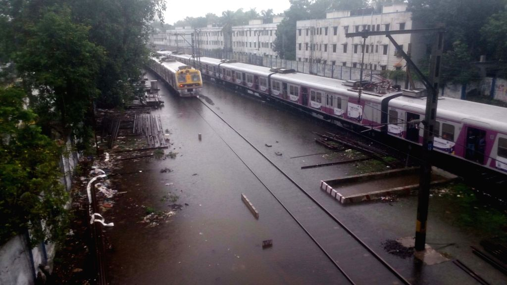 Mumbai: Heavy rains leave railway tracks water-logged, in Mumbai on July 2, 2019. (Photo: IANS)