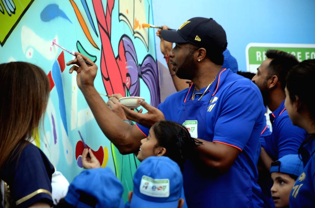 Mumbai Indians' Kieron Pollard paints a wall during a programme organised by Reliance Foundation under Education and Sports For All (ESA) initiative in Mumbai on April 11, 2019.