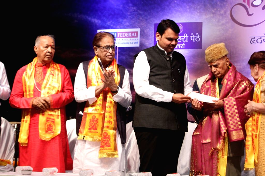 : Mumbai: Maharashtra Chief Minister Devendra Fadnavis confers this year's prestigious Hridaynath Award for Lifetime Achievement  on renowned National Award winning music director Mohammed ...
