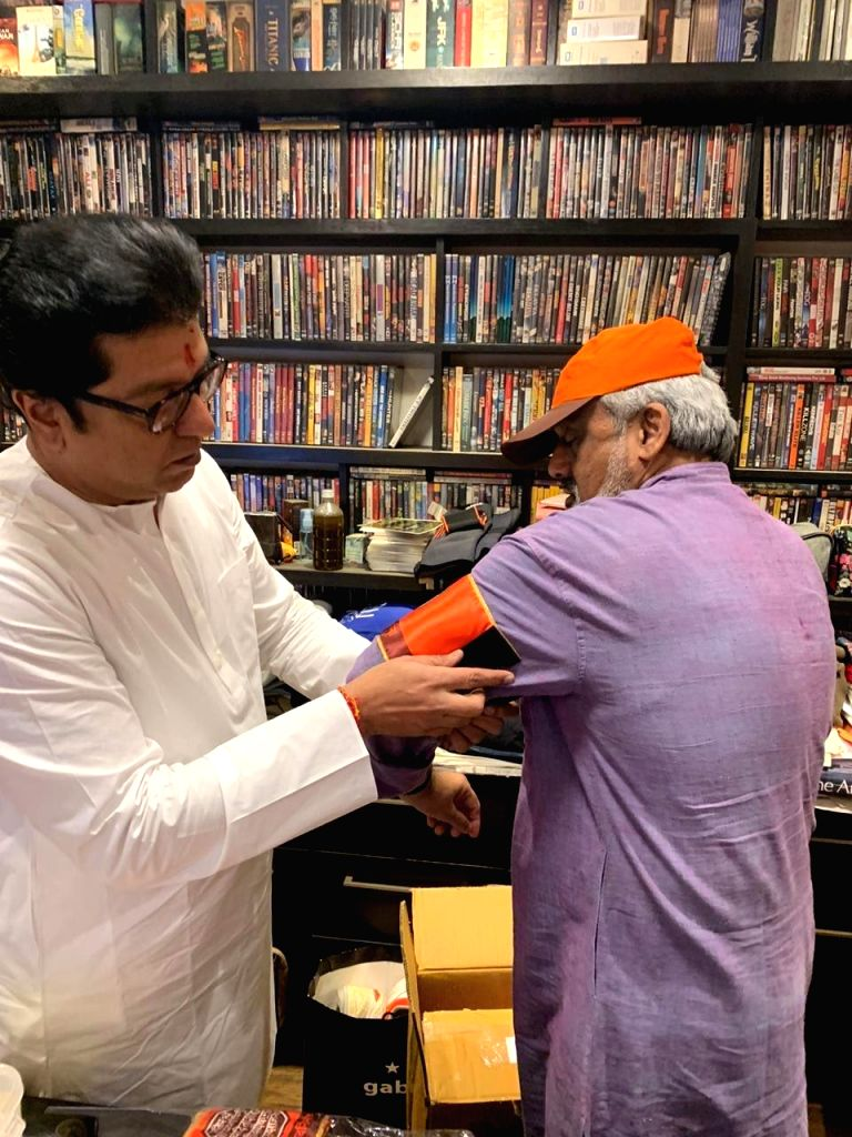Mumbai: Maharashtra Navnirman Sena (MNS) President Raj Thackeray ties the party flag arm-band to a party member before commencing his mega-morcha demanding that Pakistan-Bangladesh infiltrators must be driven out of India; in Mumbai on Feb 9, 2020. T