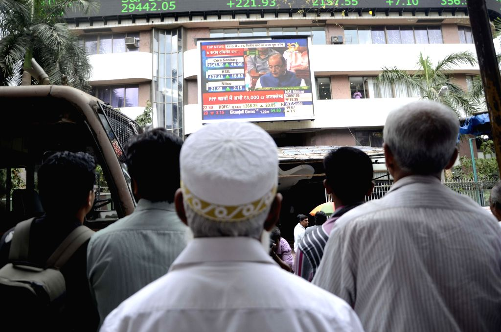 People watch Union Finance Minister Arun Jaitley present the national budget for 2015-16 on a big screen outside Bombay Stock Exchange in Mumbai on Feb 28, 2015. - Arun Jaitley