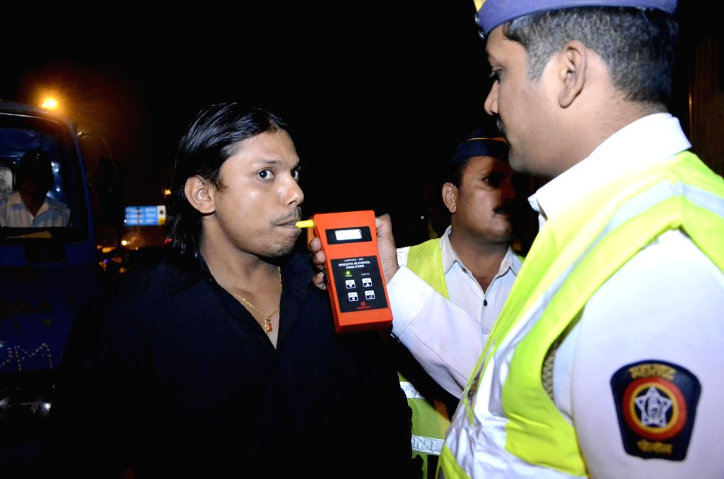 Policemen carry out breathalyser test on Mumbai drivers on the New Year's eve Dec 31, 2014.