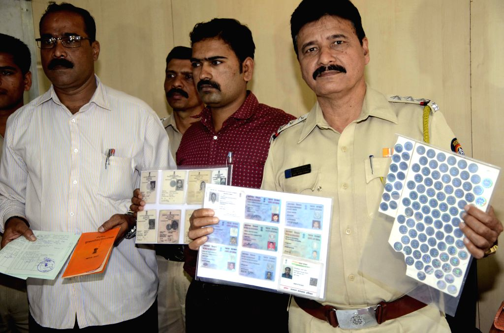 Policemen present before press the fake documents seized from a gang  in Mumbai, on Feb 27, 2015.