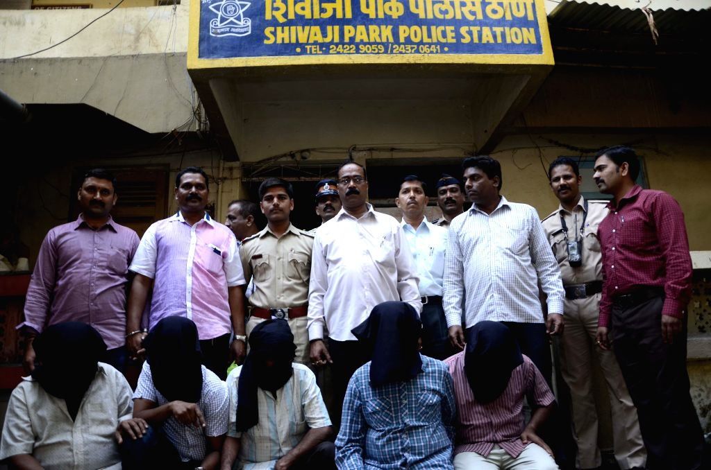 Policemen present before press the members of a gang that was involved in forgery of documents in Mumbai, on Feb 27, 2015.