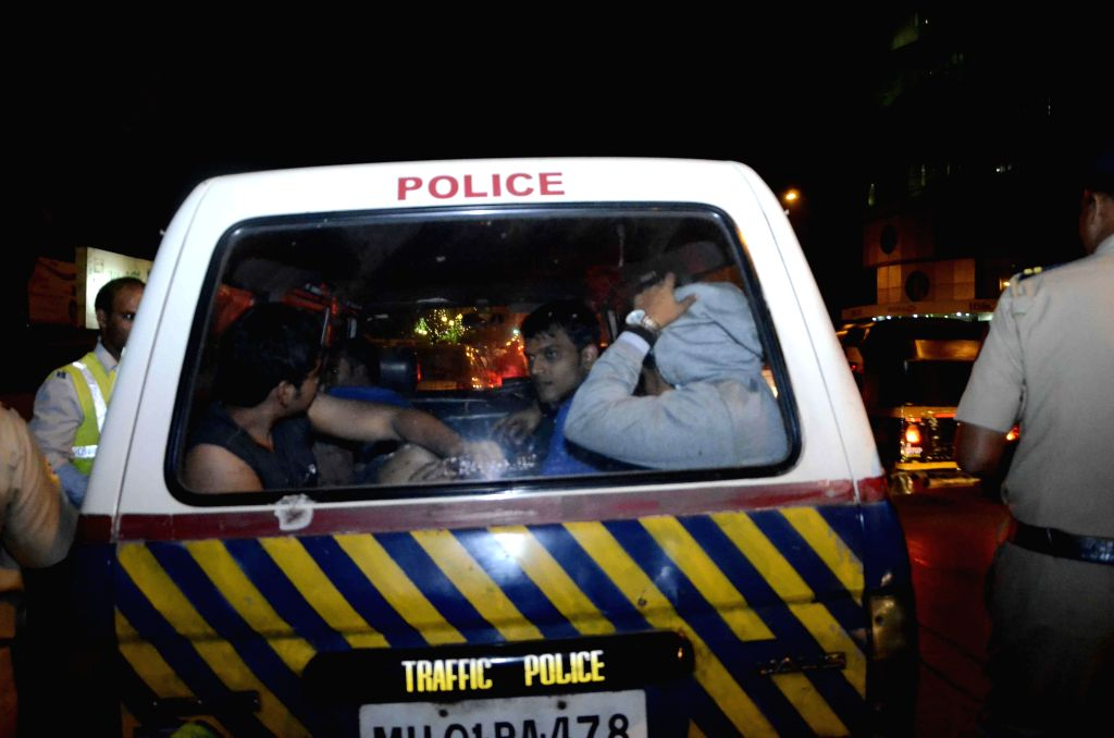 Policemen take away people who failed breathalyser test on the New Year's eve in Mumbai on Dec 31, 2014.
