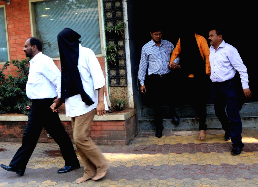 Policemen take away the arrested members of underworld don Ravi Pujari's gang, in Mumbai, on April 7, 2015.