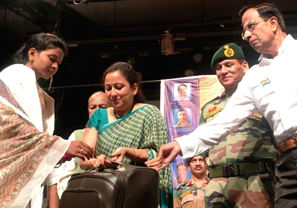 Mumbai: Pooja Selukar Poonaji being honoured by Lt.Gen. S. K. Prashar, the General Officer Commanding, Maharashtra, Gujarat and Goa; during a programme organised by Shanmukhananda Sabha to felicitate seven war widows and the parents of a martyr Sqd.