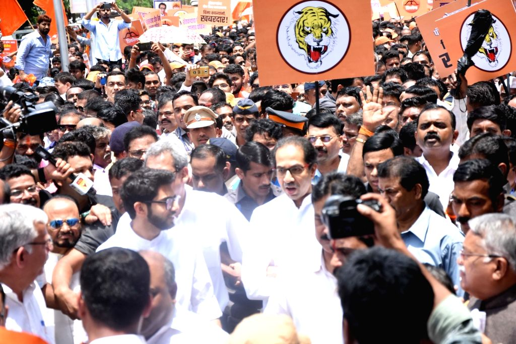 Mumbai: Shiv Sena workers led by party President Uddhav Thackeray and his son and Yuva Sena chief Aditya Thackeray participate in a procession organised by the ruling ally, targeting the high-handed attitude of various private insurance companies in