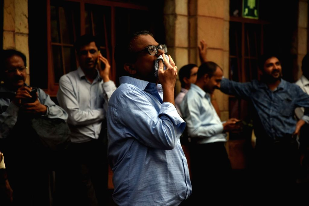 Mumbai: Traders keep a close watch on stock market outside the BSE building, in Mumbai on July 8, 2019. Disappointment over the Budget proposals and muted global markets led the Sensex to log the heaviest fall in seven months on Monday. Both the key