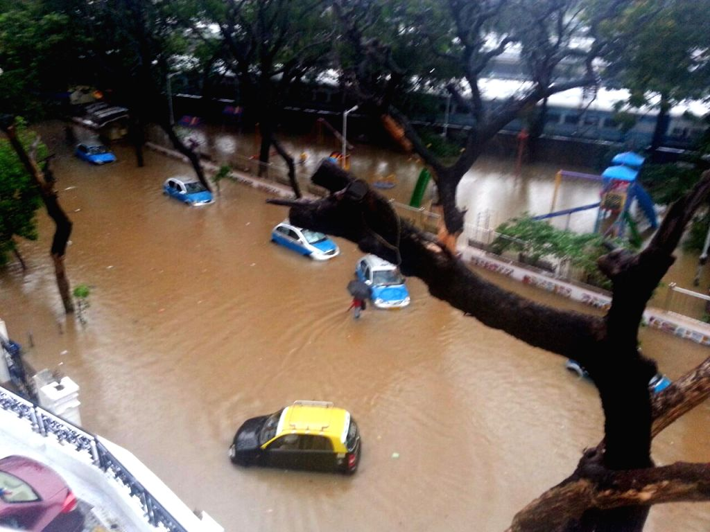 Vehicles ply on a submerged road as heavy rain hit train services in Mumbai on June 19, 2015.