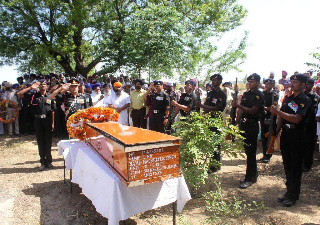 Army soldiers pay respect to L/Naik Nachhattar Singh at his village Munda Pind in Amritsar district on May 2, 2015. Nachhattar Singh was killed in a terrorist attack in Srinagar.