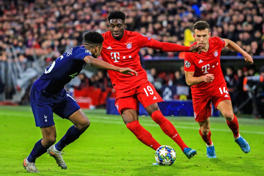 MUNICH, Dec. 12, 2019 - Alphonso Davies (C) of Bayern Munich vies with Kyle Walker-Peters (L) of Tottenham Hotspur during a UEFA Champions League Group B match between FC Bayern Munich of Germany and ...
