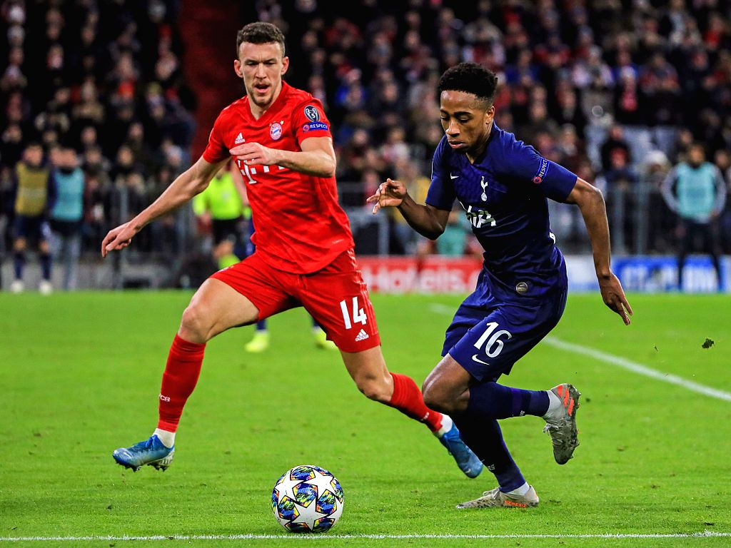 MUNICH, Dec. 12, 2019 - Kyle Walker-Peters (R) of Tottenham Hotspur controls the ball under the defense from Ivan Perisic of Bayern Munich during a UEFA Champions League Group B match between FC ...