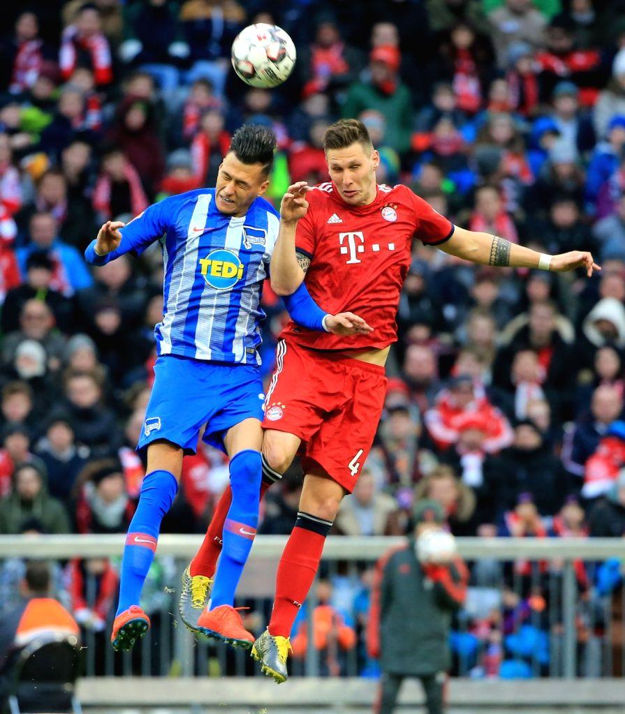 MUNICH, Feb. 24, 2019 - Bayern Munich's Niklas Suele (R) vies for header with Hertha's Davie Selke during a German Bundesliga match between Bayern Munich and Hertha Berlin in Munich, Germany, Feb. ...