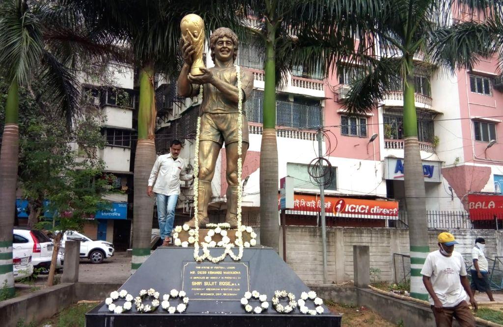 Municipal workers clean the statue of Diego Maradona, in Kolkata on Nov 26, 2020