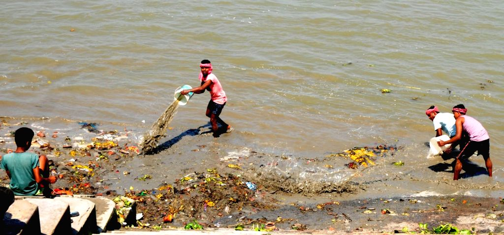 Municipal workers cleaning up river Ganga on Day 5 of the 21-day countrywide lockdown imposed to contain the spread of novel coronavirus, in Kolkata on March 29, 2020.