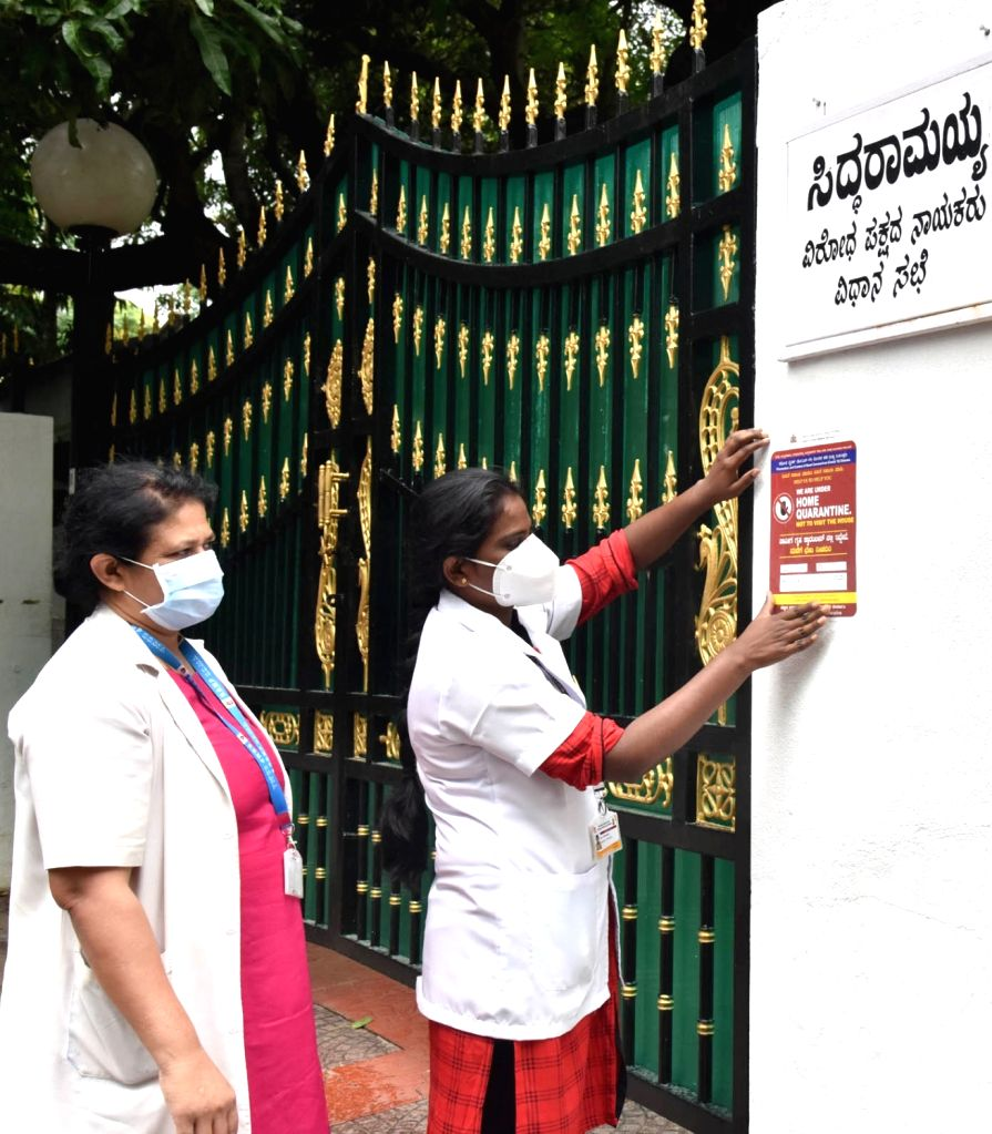 Municipal workers paste a notice of home quarantine outside the residence of Congress Legislature Party leader Siddaramaiah after he tested positive for COVD-19, in Bengaluru on Aug 4, ...