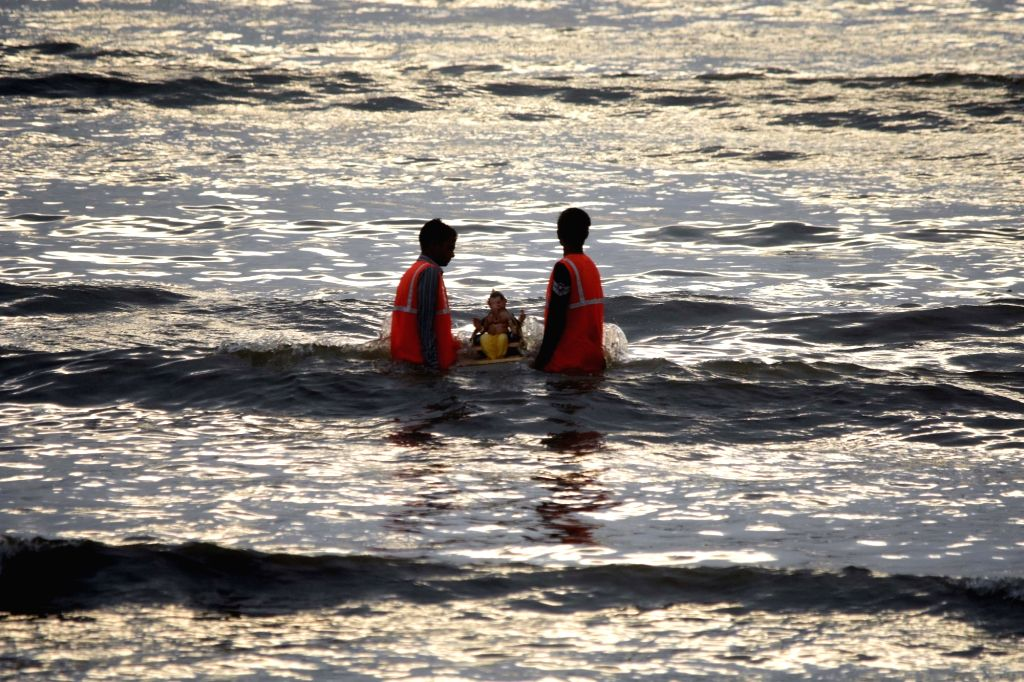 Municipal workers remove Ganesh idols immersed in the waters of the Dadar beach on Anant Chaturdashi or the last day of Ganesh Chaturthi, in Mumbai on Sep 1, 2020.
