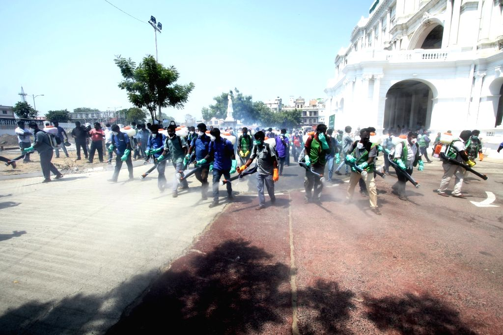 Municipal workers spray disinfectant around the building premises of Chennai Municipal Corporation as a precautionary measure to contain COVID-19 amid coronavirus pandemic, in Chennai on ...