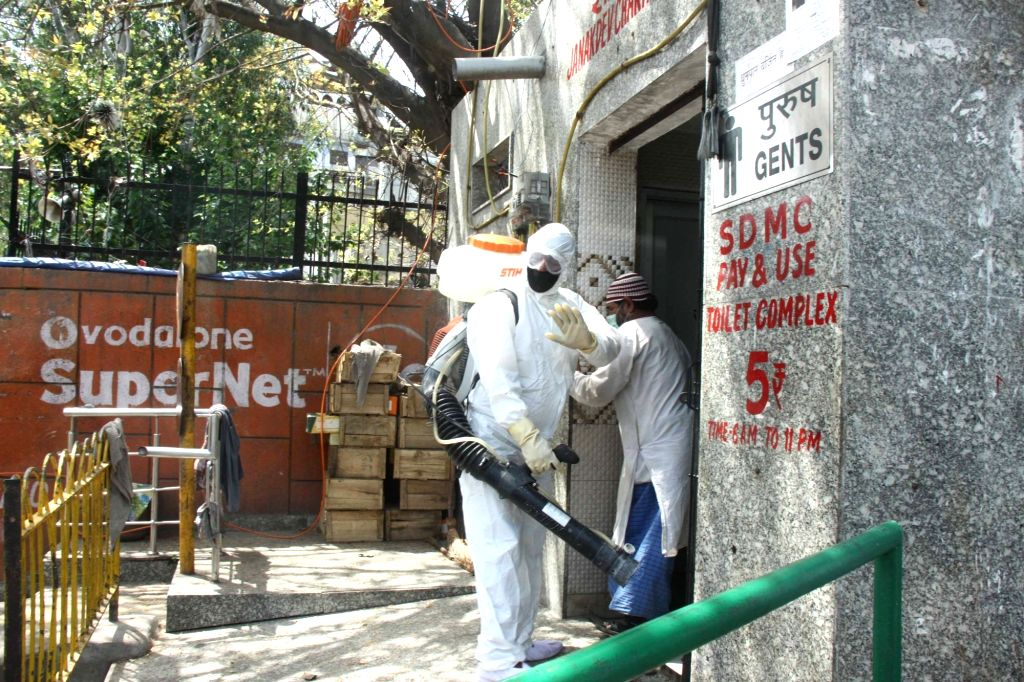 Municipal workers spray disinfectants to sanitise Delhi's Nizamuddin area where 24 cases of positive coronovirus were detected till Tuesday late night, during the 21-day nationwide ...