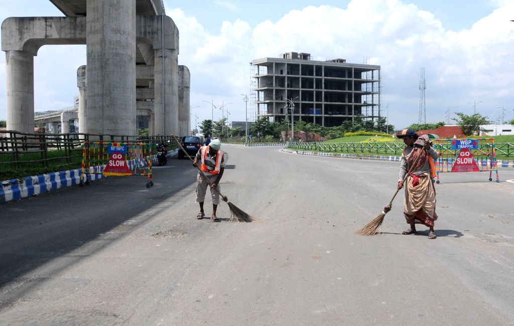 Municipal workers sweep a deserted road during the biweekly COVID-19 lockdown in Kolkata on Sep 11, 2020.