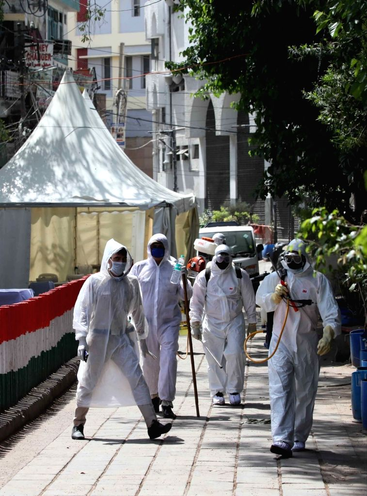 Municipal workers wearing protective gear spray disinfectants to sanitise Delhi's Nizamuddin area where 24 cases of positive coronovirus were detected till Tuesday late night, during the ...