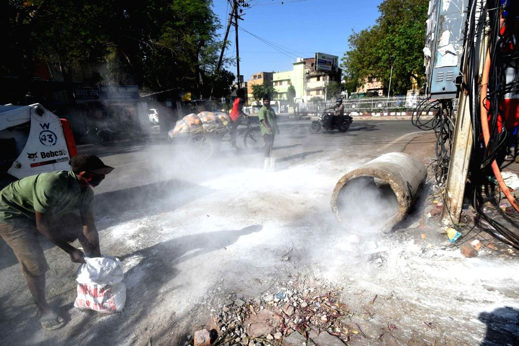 Municipality workers sprinkling anti-bacterial powder around Dinkar Golambar on Day 2 of the 21-day nationwide lockdown imposed by the Narendra Modi government over the coronavirus pandemic; ... - Narendra Modi
