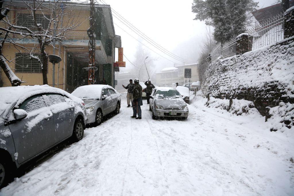 MURREE, Jan. 14, 2017 - People walk on a snow-covered street in Murree, Pakistan, Jan. 14, 2017.