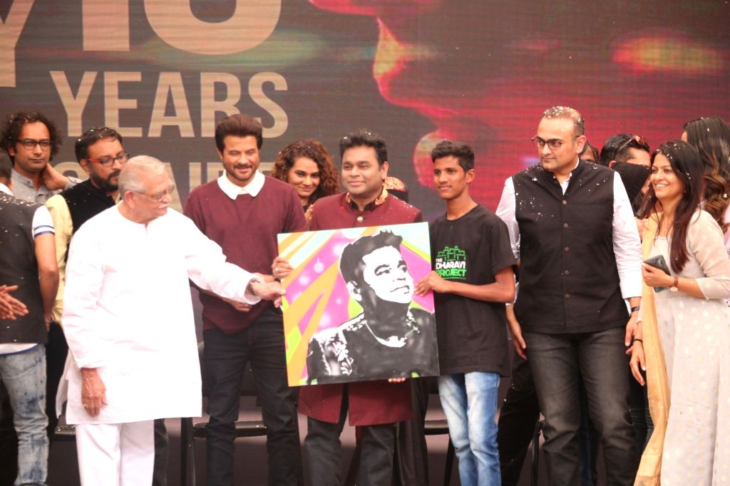 """Music Director A.R. Rahman being presented with his portrait by a fan during the 10-year celebration of the music of """"Slumdog Millionaire"""" that won eight awards at the Oscars, in ..."""