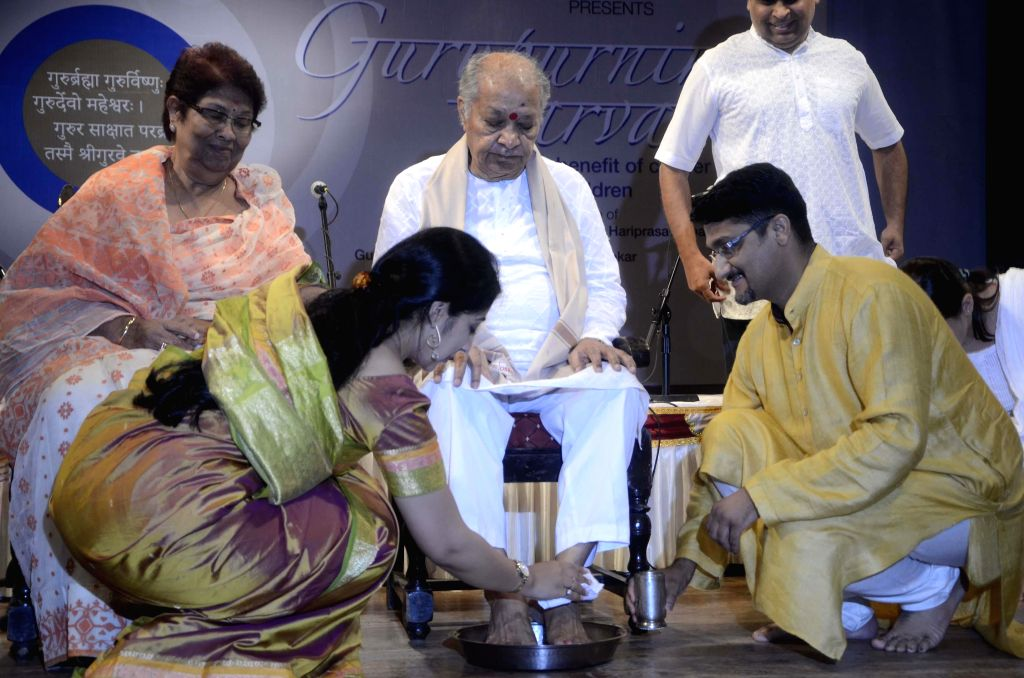 Musicians wash the feet of Indian classical flautist Pandit Hariprasad Chaurasia during a programme organised on Guru Purnima at Veer Savarkar Rashtriya Auditorium in Mumbai on July 13, 2014.