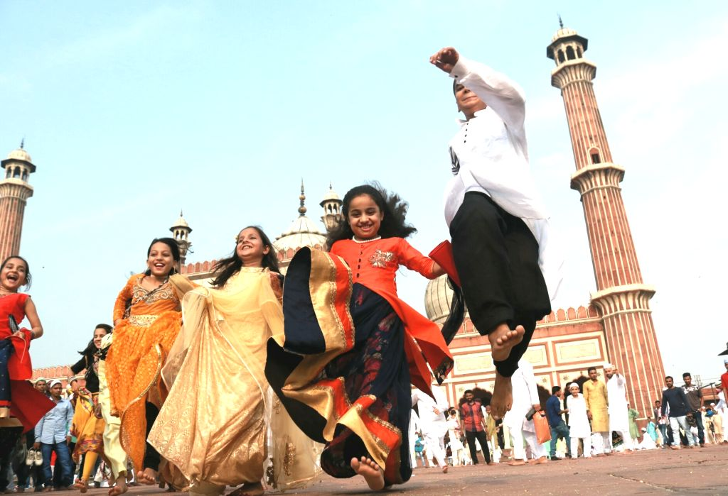 Muslim children offer greetings after the prayer on the occasion of Eid-ul-Fitr, at Jama  Masjid in New Delhi on June 26, 2017.