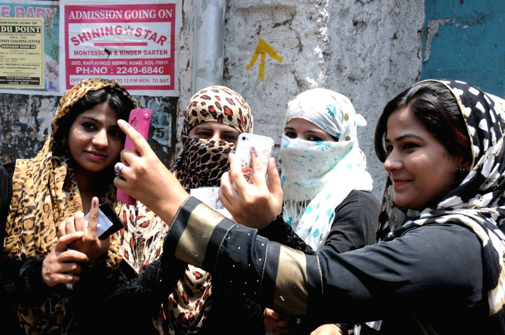 Muslim women showing their finger marked with phosphorous ink after casting their vote at the polling station during the West Bengal Assembly Election in Kolkata on April 21, 2016.
